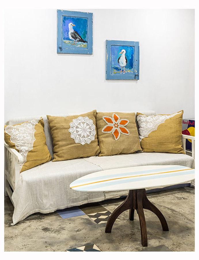 Na sala de estar gaivotas e pranchas de surf decoram o ambiente