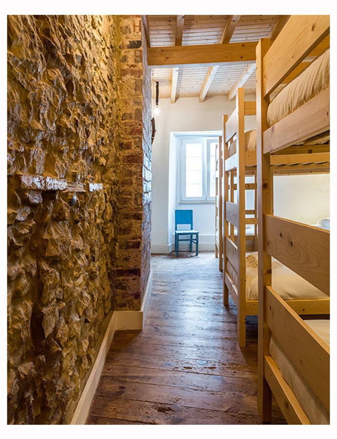 O quarto com paredes em pedra recuperadas
