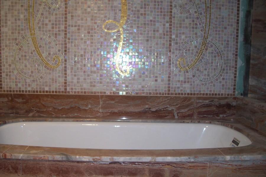 Parede revestida com pastilha decorativa e banheira em marmore