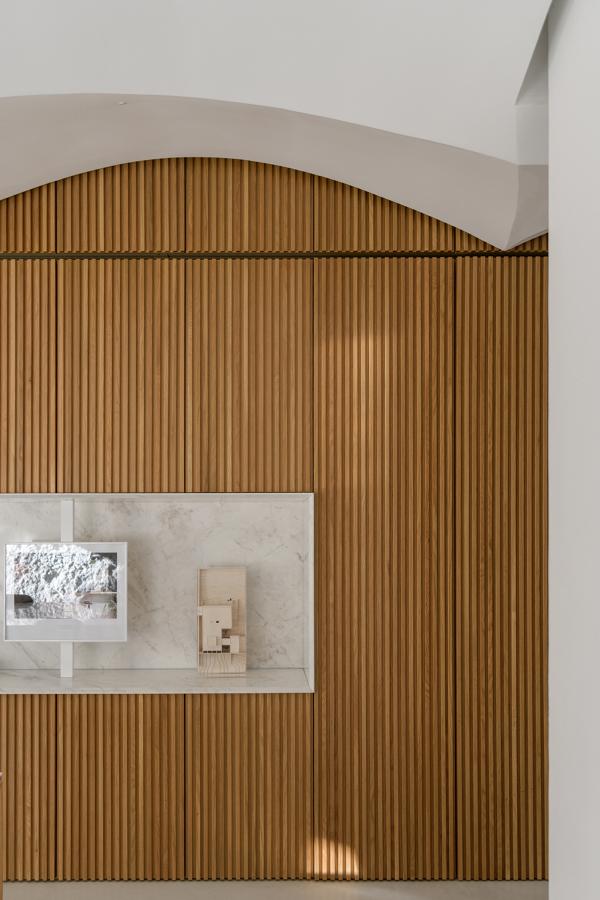 Pormenor da parede de madeira ripada de armarios com nicho de pedra e tecto