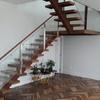Escada interior com estrutura de metal ou madeira, degraus de madeira e corrimão de vidro